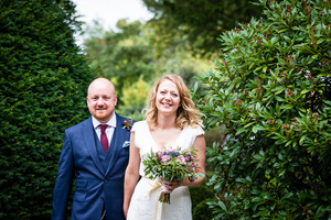 Manchester bride and groom walking through trees at Didsbury House Hotel