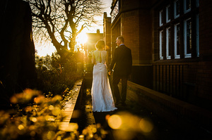 Cheshire bride walking in sunset holding hands at Altrincham Town Hall